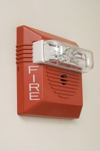 Red fire alarm mounted on white wall